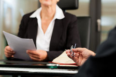Female Lawyer or notary in her office. Mature female lawyer or notary with client in her office for counseling stock photography