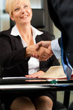 Female Lawyer or notary in her office. Mature female lawyer or notary with client in her office - handshake royalty free stock image