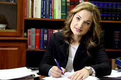 Female lawyer in office. Portrait of a female lawyer in a boutique law firm signing documents