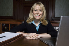 Female Lawyer Sitting With Laptop And Documents. Portrait of a happy female lawyer with laptop and documents in courthouse stock images