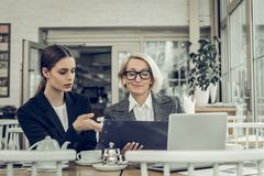 Female lawyer speaking with her secretary sitting in restaurant. Female lawyer. Successful female lawyer speaking with her secretary sitting in restaurant royalty free stock photography