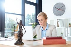 Female lawyer working with laptop. Serious mature female lawyer working with laptop at modern office royalty free stock image