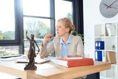 Female lawyer at workplace. Thoughtful female lawyer at workplace with pen and paperwork Stock Photography