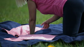 Female laying down the napkins on a blanket for a picnic. Female preparing everything for a picnic on the blue blanket stock video footage