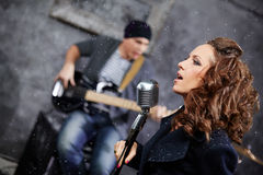 Female lead vocalist and guitarist in studio Stock Images