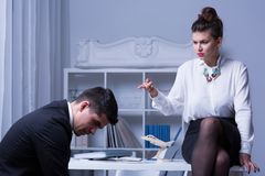Female leader humiliating male worker. Photo of female leader humiliating male corporate worker royalty free stock photos