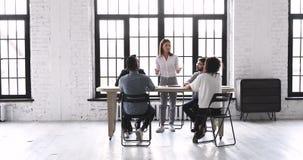 Female leader speaking at team briefing in modern office space