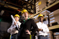 Female leading construction crew. Workers with hard hats standing in warehouse holding plans Stock Photography