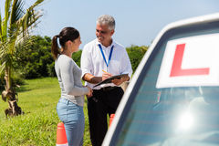 Female learner driver instructor. Female learner driver and instructor behind a car royalty free stock images