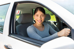 Female learner driver. Pretty female learner driver looking out of the car window Royalty Free Stock Images