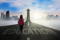 Female learner on the education way. Young student walking on the road with an Education text turning into arrow upward, symbolizing the way to gain higher royalty free stock photography
