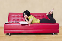 Female learner studying while lying on sofa Royalty Free Stock Photos