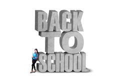 Female learner and a text of back to school. Attractive female learner standing near the text of back to school, on whitep stock photo