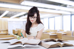 Female learner writing on the book in class Royalty Free Stock Photography
