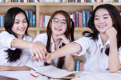 Female learners joining hands in library Royalty Free Stock Photos
