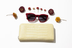 Female  leather purse and sunglasses. Yellow female leather purse with red sunglasses lie surrounded by flowers on a white background Royalty Free Stock Photo