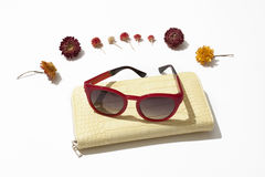 Female  leather purse and sunglasses. Yellow female leather purse with red sunglasses lie surrounded by flowers on a white background Stock Image