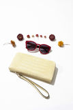 Female  leather purse and sunglasses. Yellow female leather purse with red sunglasses lie surrounded by flowers on a white background Stock Photo