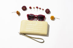 Female  leather purse and sunglasses. Yellow female leather purse with red sunglasses lie surrounded by flowers on a white background Royalty Free Stock Image