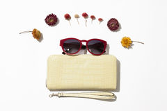 Female  leather purse and sunglasses. Yellow female leather purse with red sunglasses lie surrounded by flowers on a white background Royalty Free Stock Images