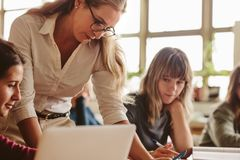 Female lecturer helping student during her class stock images