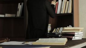 Female lecturer working with books in a library in college. tired student preparing for exams stock video