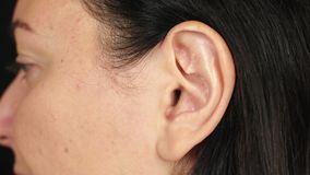Female left ear close up. Ear of adult brunette woman. Parts of face and body