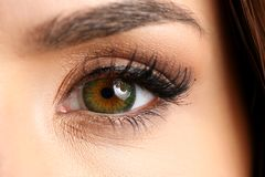 Female left emerald green coloured eye extreme closeup. Low light technique oculist and perfect vision contact lens shadow makeup cosmetics mascara concept royalty free stock photos