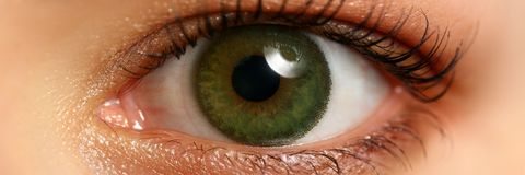 Female left emerald green coloured eye extreme closeup. Low light technique oculist and perfect vision contact lens correction beauty shadow makeup cosmetics royalty free stock photos