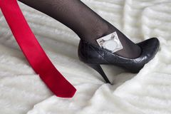 Female leg, condom, tie royalty free stock photography