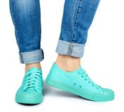 Female leg in jeans and sneakers isolated on white background.  royalty free stock photography