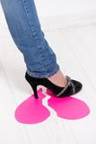 Female leg treading paper heart. Female leg wearing jeans and high heel shoes treading on torn paper heart royalty free stock photo