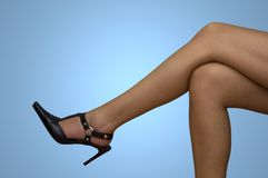 Female legs. Isolated on blue background Royalty Free Stock Photography