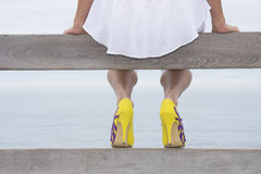 Female legs abd high heel shoes at ocean Stock Photos