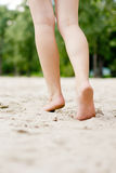 Female legs on a beach background Royalty Free Stock Images