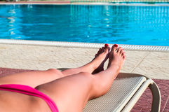 Female legs on beach bed Stock Photos