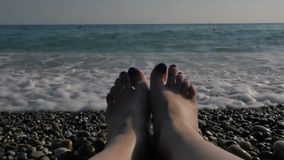 Female legs on the beach by the sea. Rest by the sea. Large transparent waves with foam. Sea pebble beach with colorful. Stones. Slow motion stock video footage