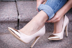 Female legs in a beautiful peach high-heeled shoes with gold nose. close-up. hands corrected jeans. Royalty Free Stock Image