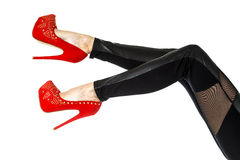 Female legs in black leggings and red high heels shoes. Female legs wearing black leggings in wetlook style and red high heels shoes with golden rivets and stock images