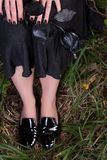 Female legs in black patent leather shoes on the grass. Black skirt and a rose. In his hand Stock Image