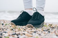 Female legs in black shoes and jeans Stock Photos