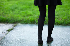 Female legs in blck tights and skirt on rainy wet park path and grass retro colors Royalty Free Stock Photography