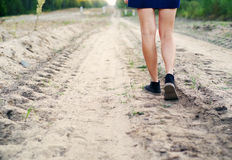 Female legs in blue boots on the sandy dusty road leaving afar Stock Images