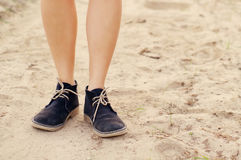Female legs in blue boots on the sandy dusty road Stock Photo
