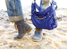 Female legs in blue jeans and boots with a blue bag on a background of the sandy beach Stock Image