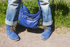 Female legs in blue jeans and boots with a blue bag on a summer background of a green grass Royalty Free Stock Photo