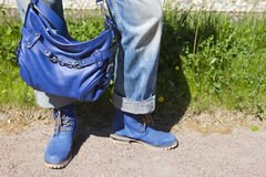 Female legs in blue jeans and boots with a blue bag on a summer background of a green grass Stock Photography