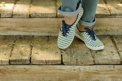 Female legs in blue jeans and striped sneakers on old wooden ste. Ps. Selective focus Stock Photos