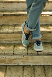 Female legs in blue jeans and striped sneakers on old wooden ste. Ps. Selective focus Royalty Free Stock Photo