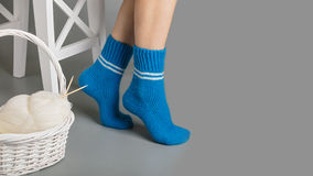 Female legs in blue knitted socks near the basket with yarn and Royalty Free Stock Photography